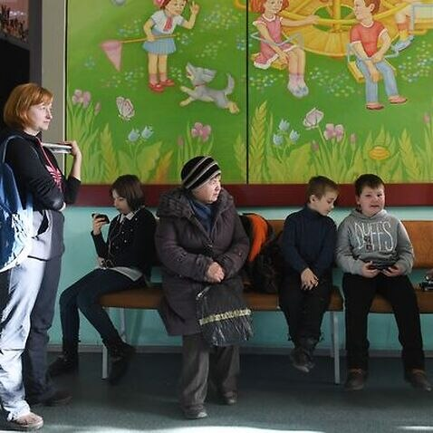 Children wait in a queue for vaccination against measles in Kiev