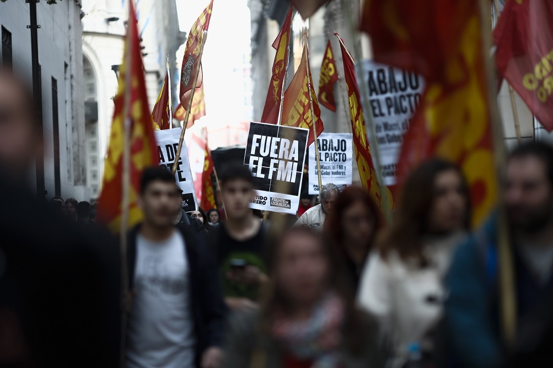 Dozens of protesters march outside the Central Bank, in Buenos Aires.