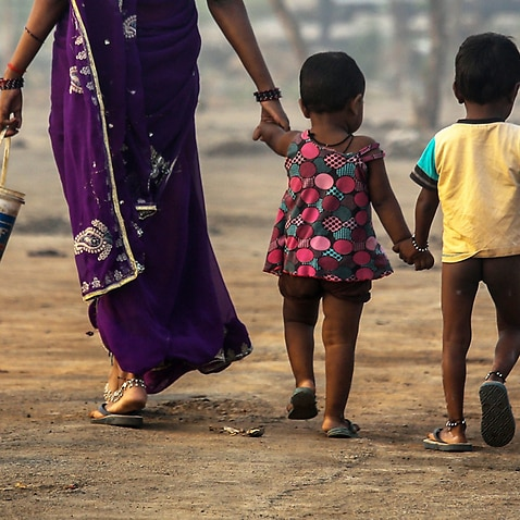 An Indian woman walks with her children
