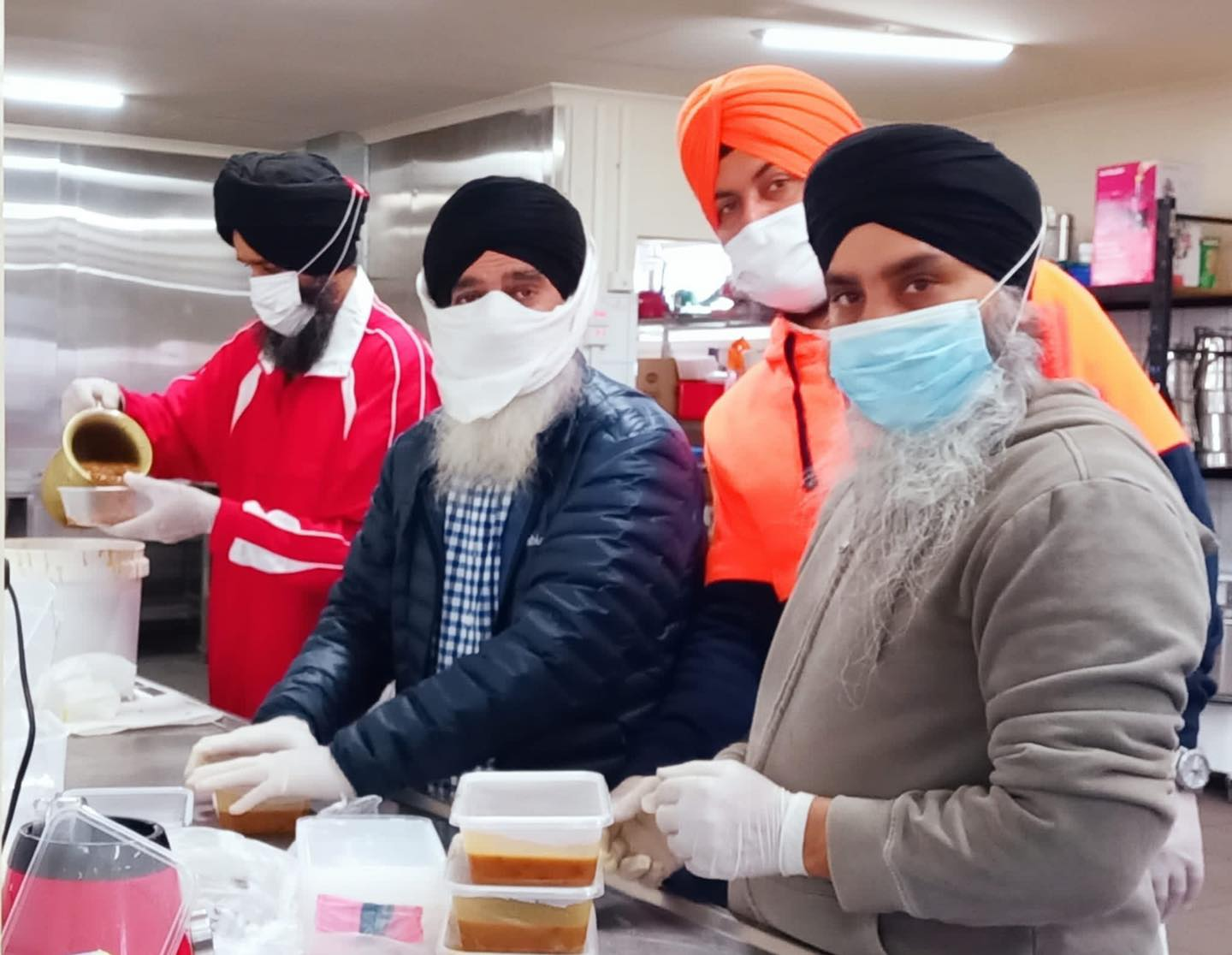 Sikh volunteers packaging food containers for distribution.