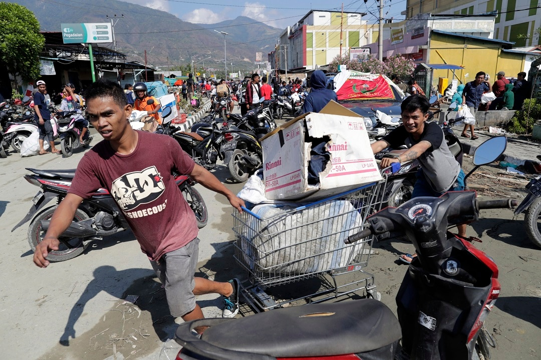Indonesian men drag a shopping trolley with goods looted from a tsunami-devastated shopping mall in Palu.