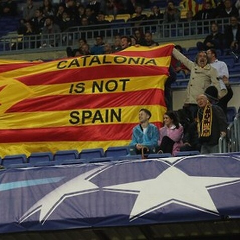 Pro-independence supporters hold a Catalan flag at the Camp Nou