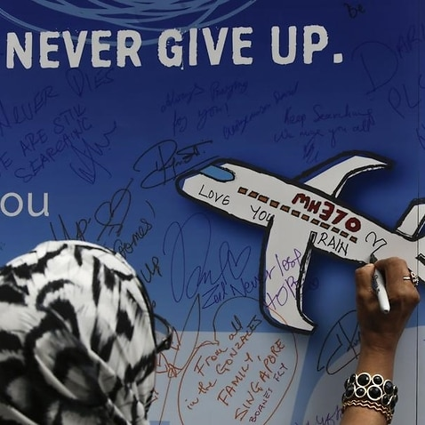 A woman writes messages on a banner for missing flight MH370