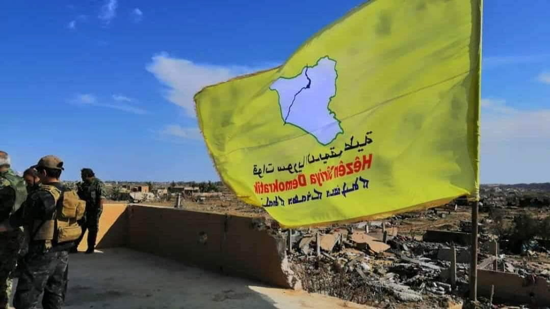 The yellow flag of US-backed Syrian Democratic Forces (SDF)  raised in the village of Baghuz, Syria, after the defeat of IS fighters.