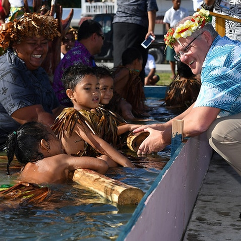 Children symbolically representing climate change greet Prime Minister Scott Morrison as he arrives for the Pacific Islands Forum