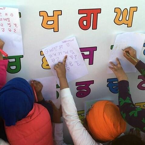 Australian children writing the Punjabi alphabet at an event in Melbourne
