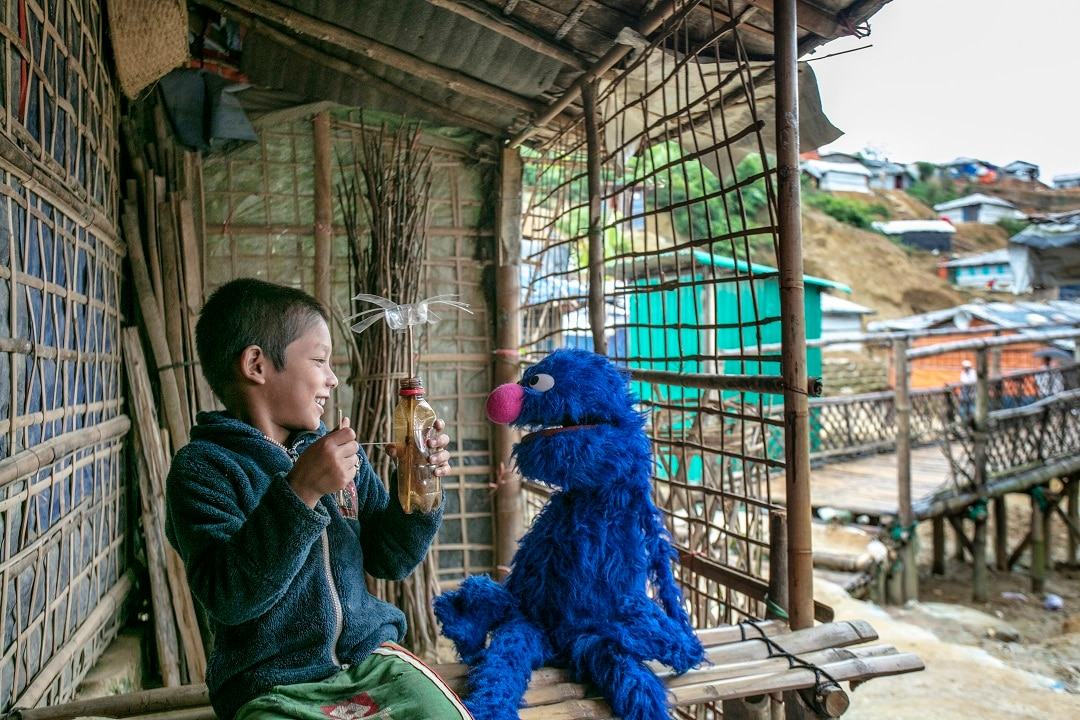 A youth plays with a Grover doll at a Rohingya refugee camp in Bangladesh.