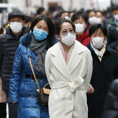 Chinese tourists wear masks in Tokyo amid the spread of pneumonia caused by a new coronavirus in the city of Wuhan