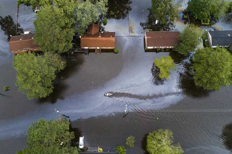 Two people in a canoe paddle through a street that was flooded by Hurricane Florence north of New Bern, North Carolina USA.