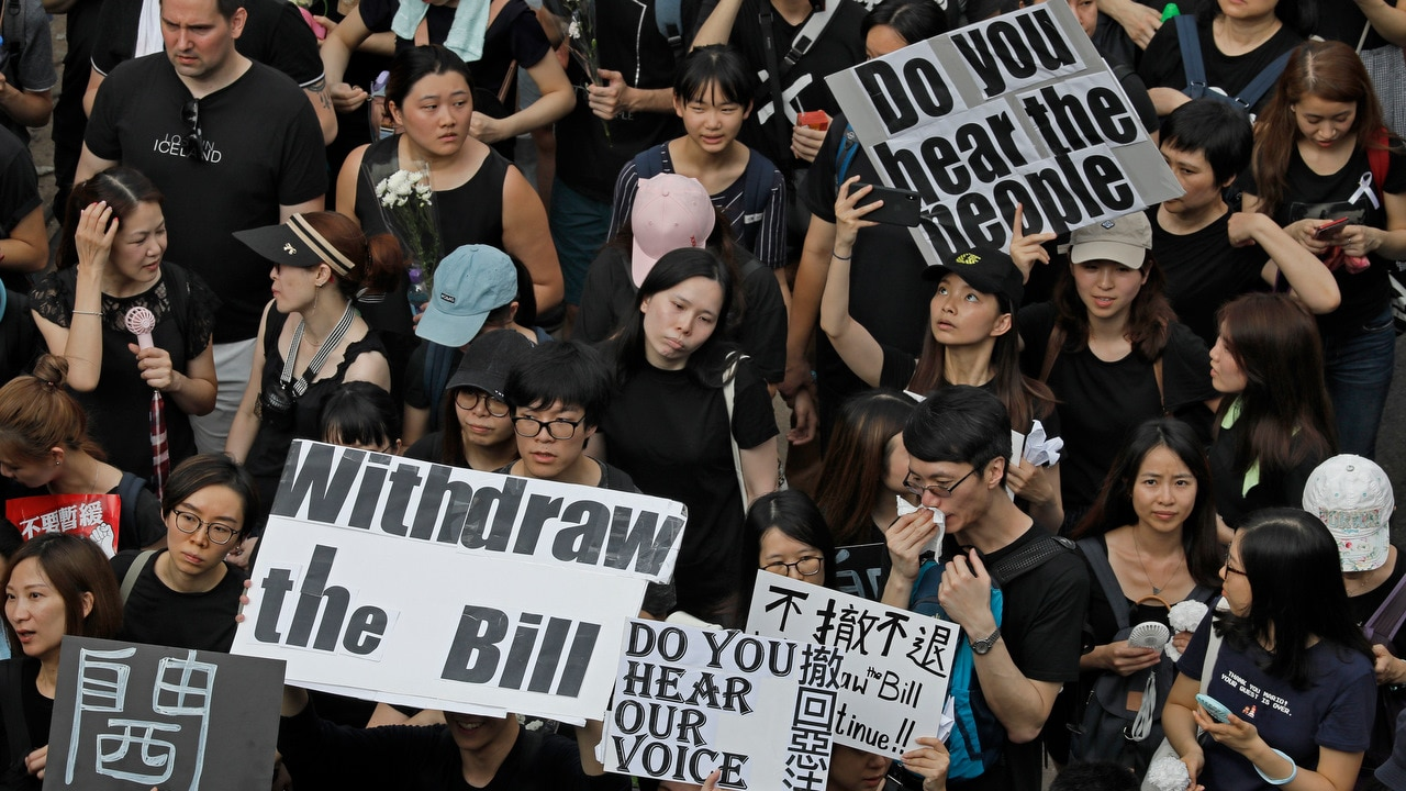Protesters raise placards as they march on the streets against an extradition bill in Hong Kong.
