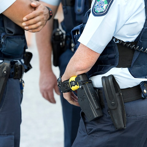 Stock photograph of a Queensland Police Officers wearing hand guns
