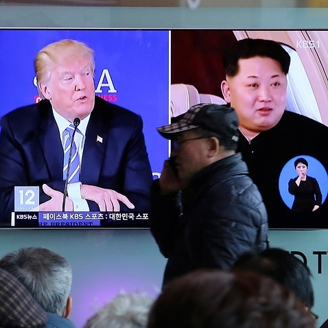 A man passes by a TV screen showing file footage of U.S. President Donald Trump, left, and North Korean leader Kim Jong-un