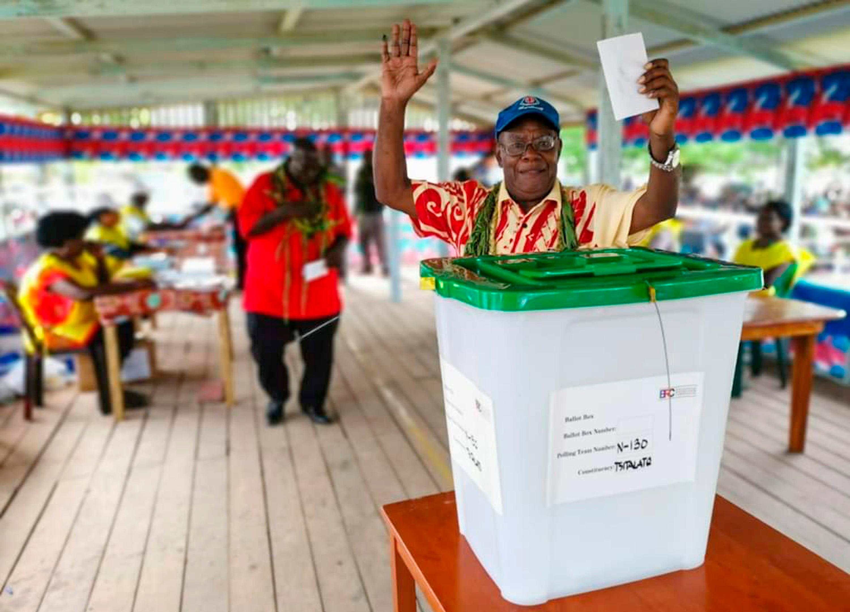 A man raises his hands as he prepares to cast a vote in Buka, the Autonomous Region of Bougainville.