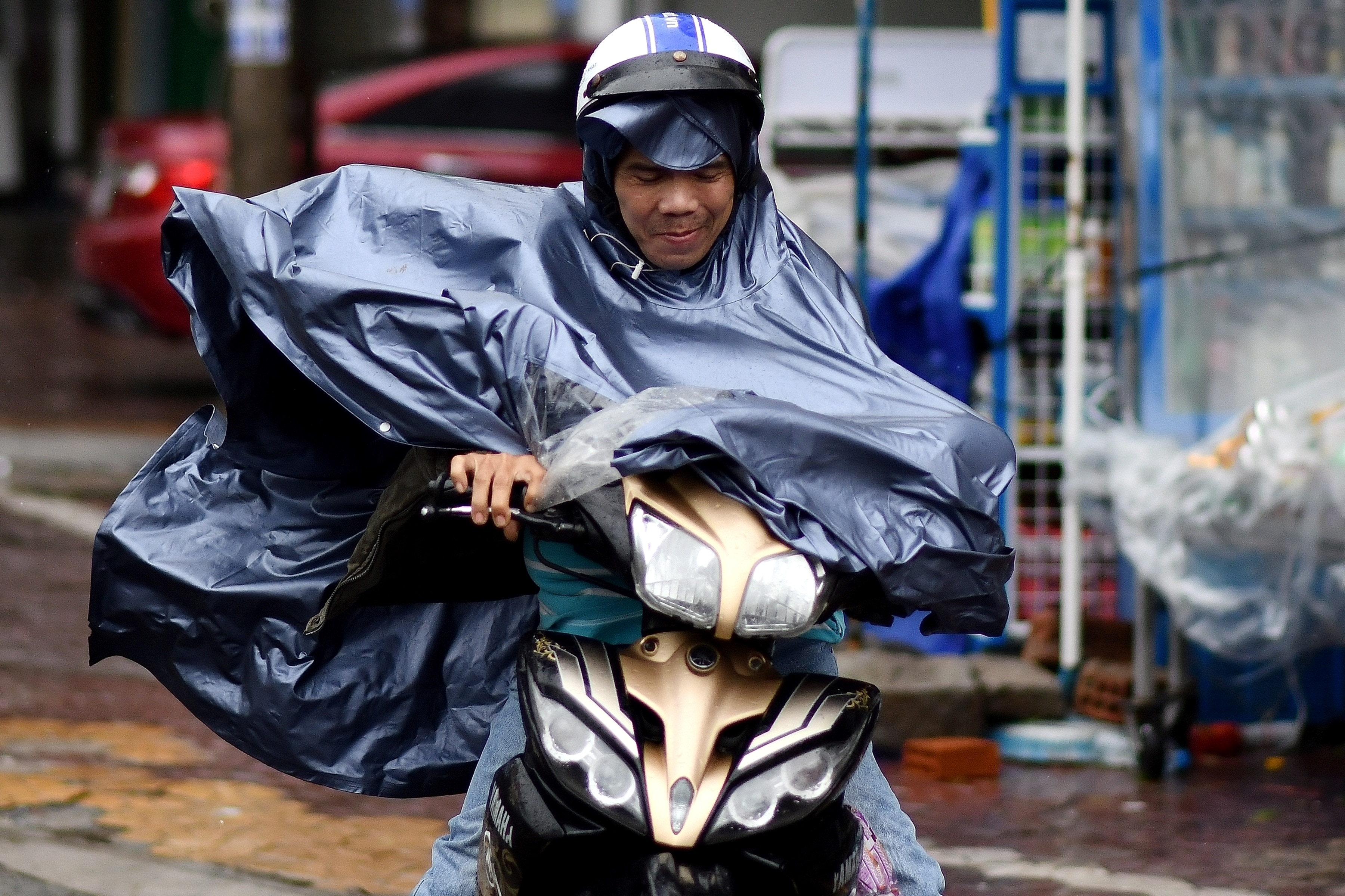 A motorist braves strong winds while riding along a street in central Vietnam's Quang Ngai province on October 28, 2020, as Typhoon Molave makes landfall.