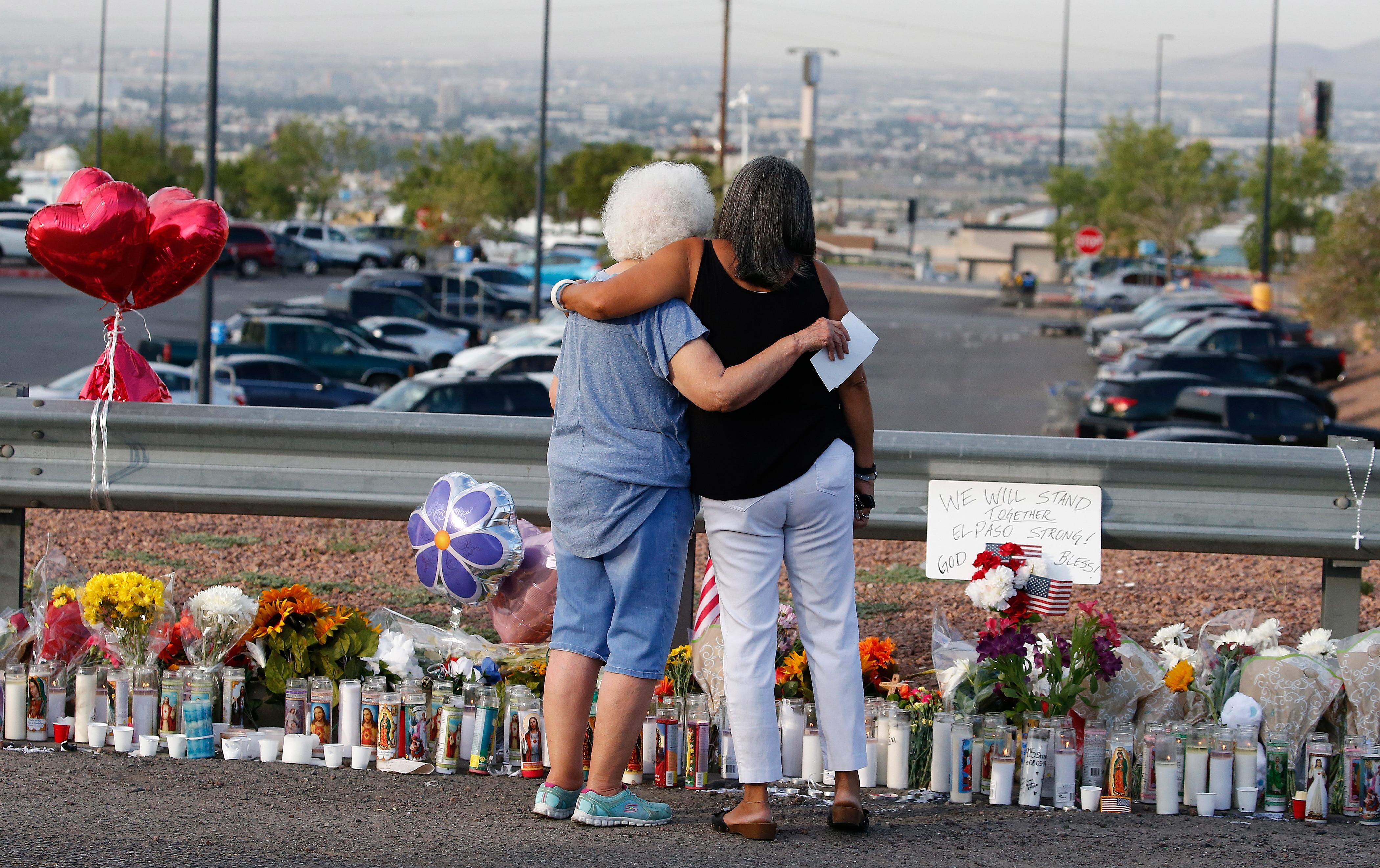 Emma Del Valle hugs Brenda Castaneda at a make shift memorial in El Paso.