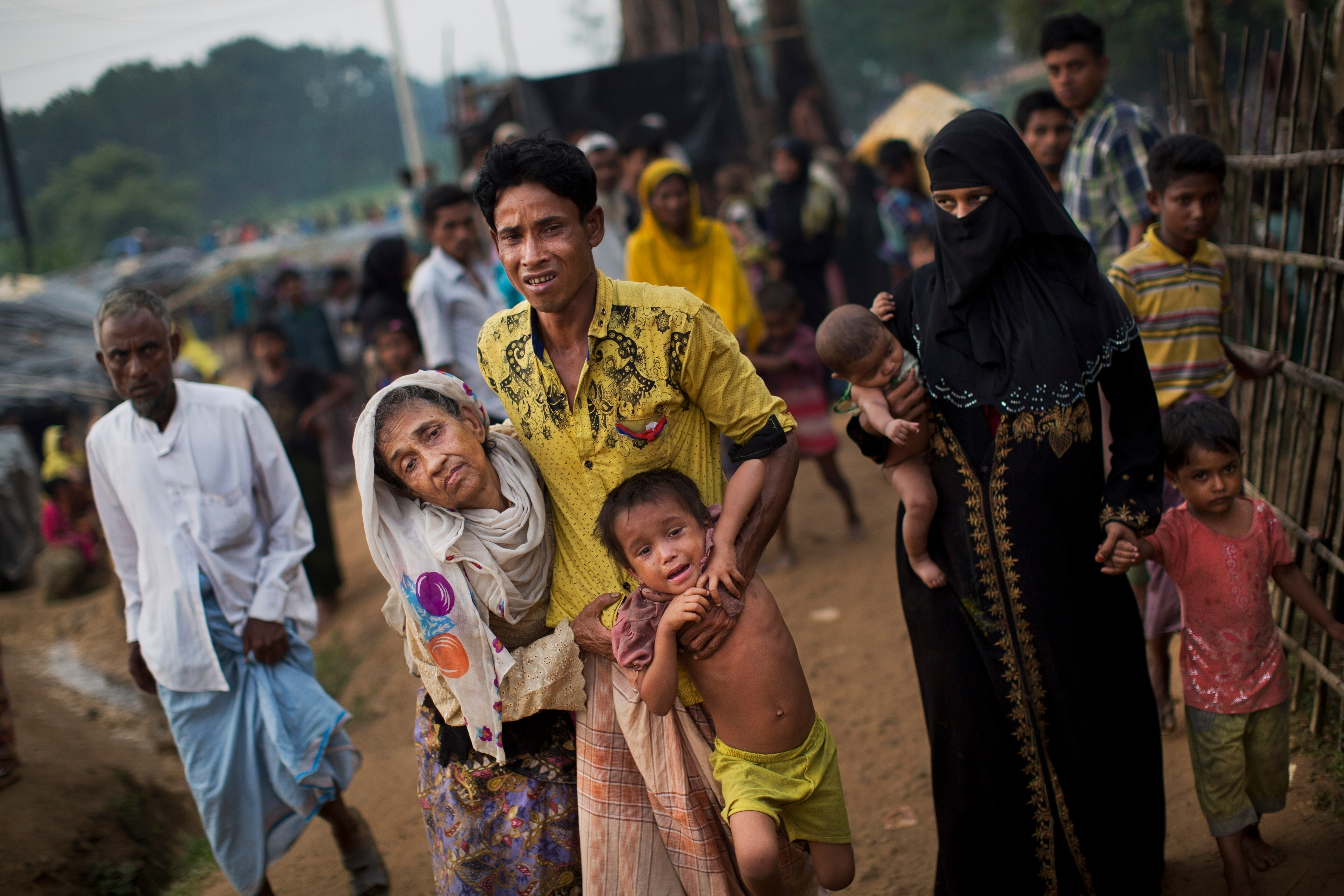 An exhausted Rohingya helps an elderly family member in 2017 as they arrive at refugee camp after crossing from Myanmar to Bangladesh.