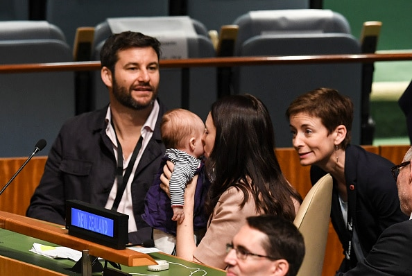 Mum and bub share a cuddle after the NZ PM addressed the meeting.