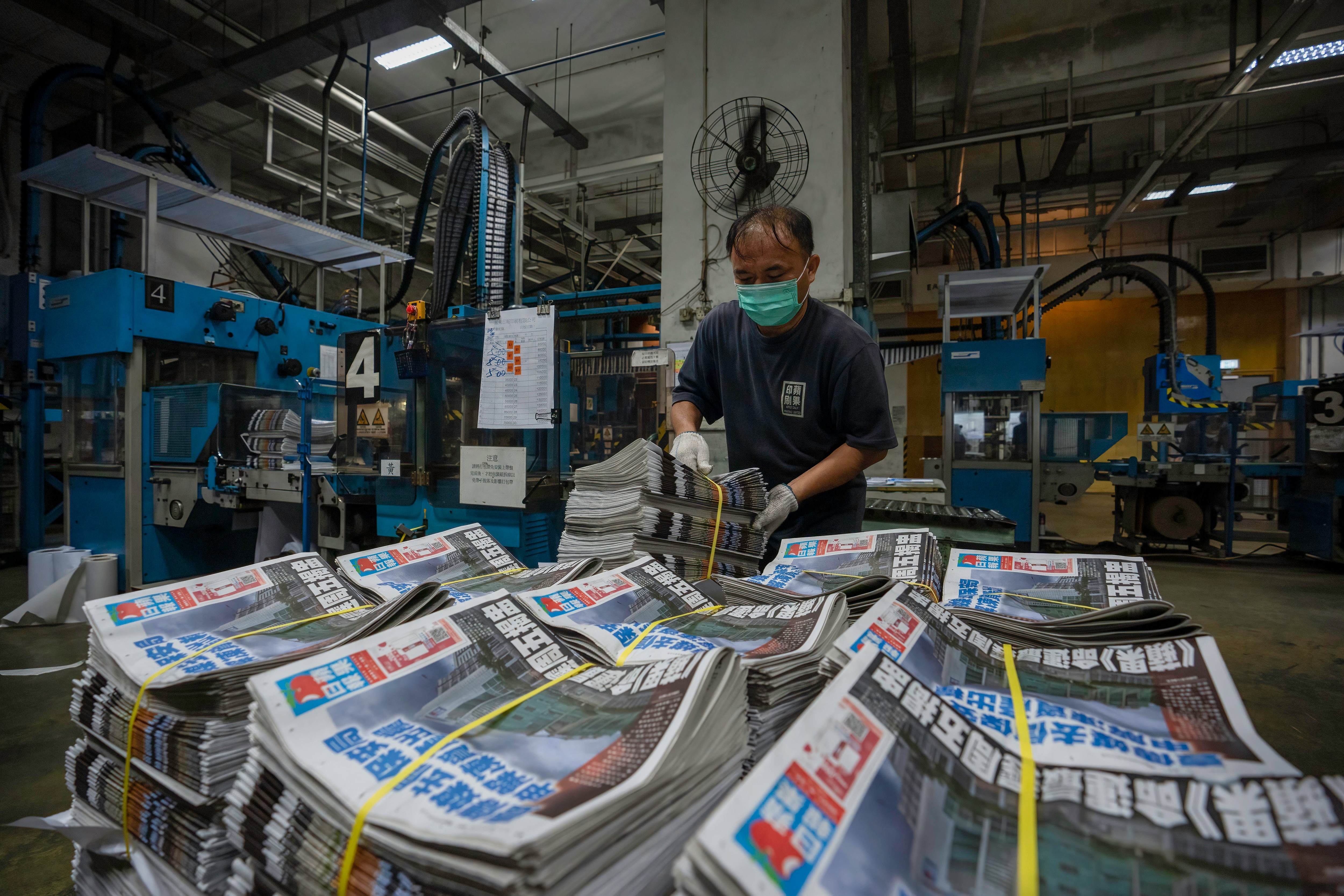An employee stacks freshly printed newspapers onto a pallet in the Apple Daily printing facility in Hong Kong.