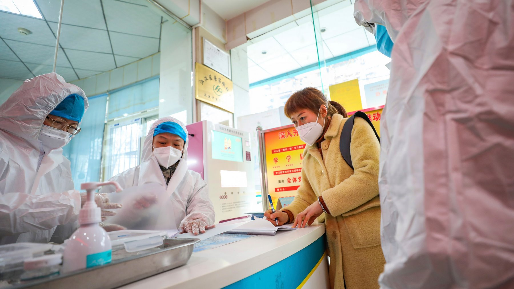 Medical workers in protective gear talk with a woman suspected of being ill with a coronavirus at a community health station in Wuhan
