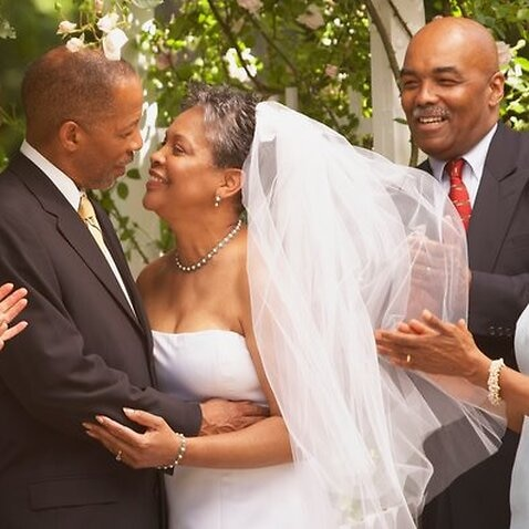Middle-aged African bride and groom hugging