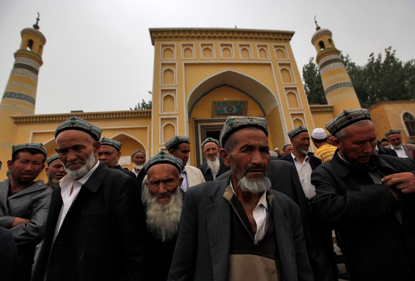Muslim men of the Uighur ethnic group leave the Id Kah Mosque after Friday prayers in Kashgar, Xinjiang