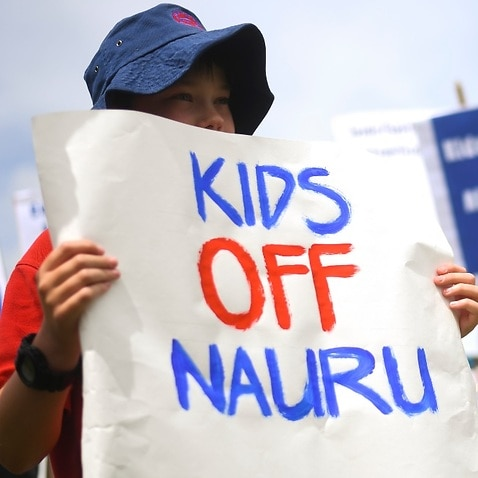 Protesters hold up signs during a rally demanding the resettlement of kids held on Nauru outside Parliament House in Canberra, Tuesday, November 27, 2018.