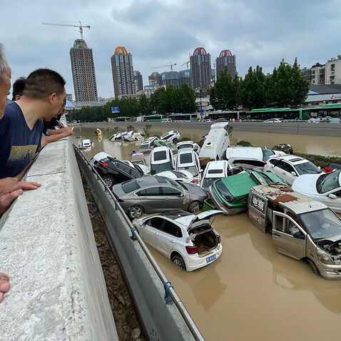 People look out at cars sitting in floodwaters after heavy rains hit the city of Zhengzhou in China's central Henan province on July 21, 2021