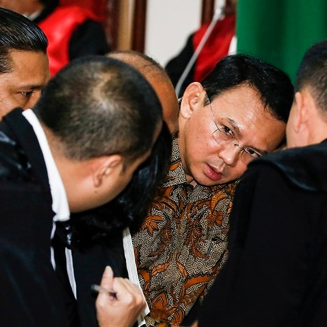 Jakarta's governor Basuki Tjahaja Purnama popularly known as 'Ahok' (C) talks to his lawyers inside the courtroom during his blasphemy trial