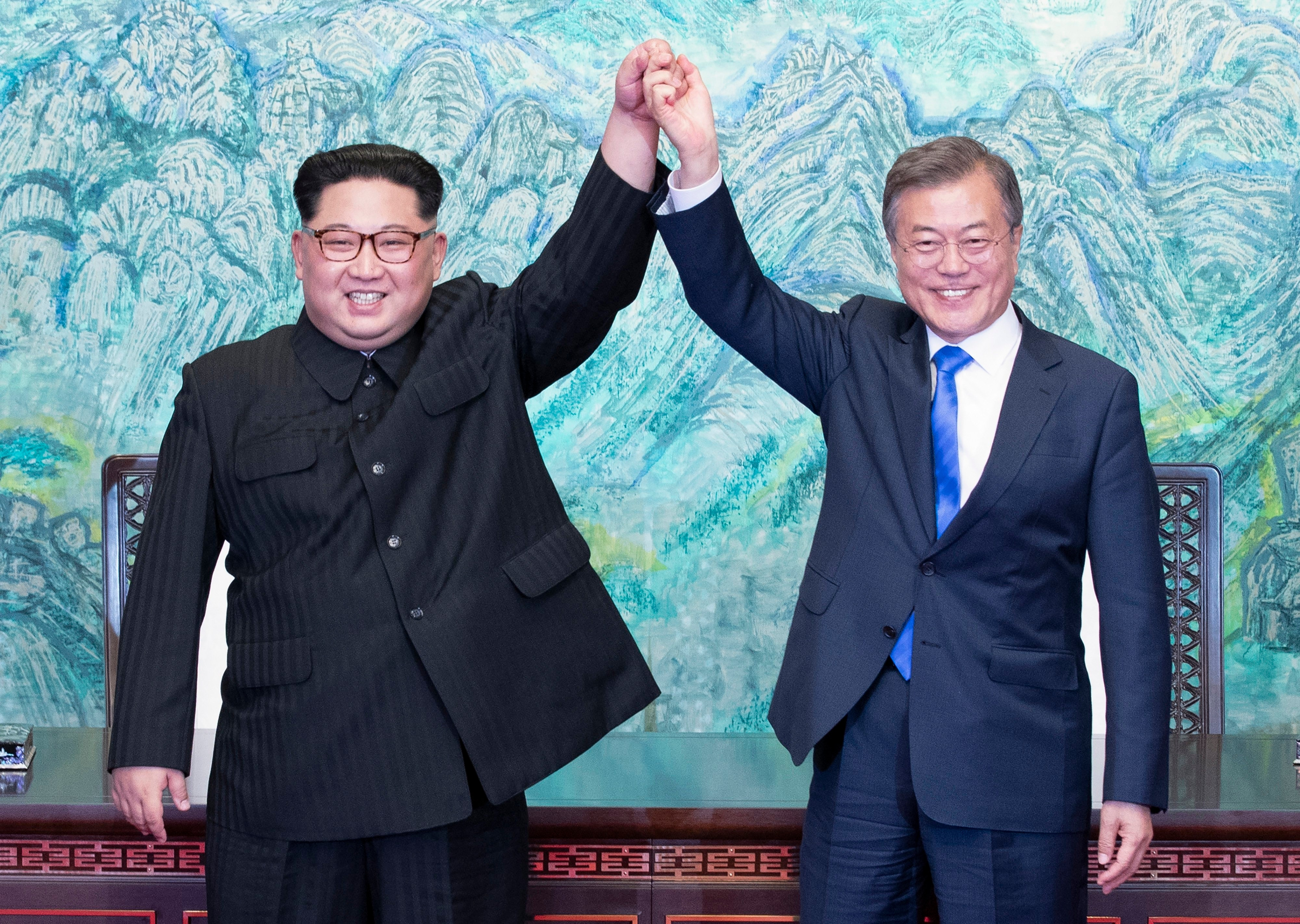 North Korean leader Kim Jong-Un and South Korean President Moon Jae-In join hands after signing a document at the Joint Security Area on the DMZ.