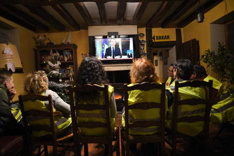 Yellow vest protesters listen to French President Emmanuel Macron speaking during a special address to the nation.