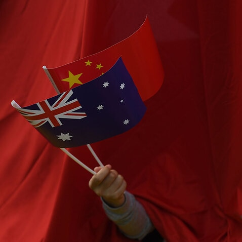 A person waving the Chinese and Australian flags.
