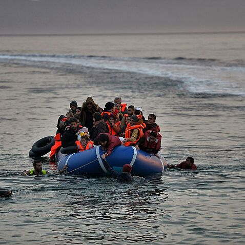 Refugees and migrants massed onto an inflatable boat