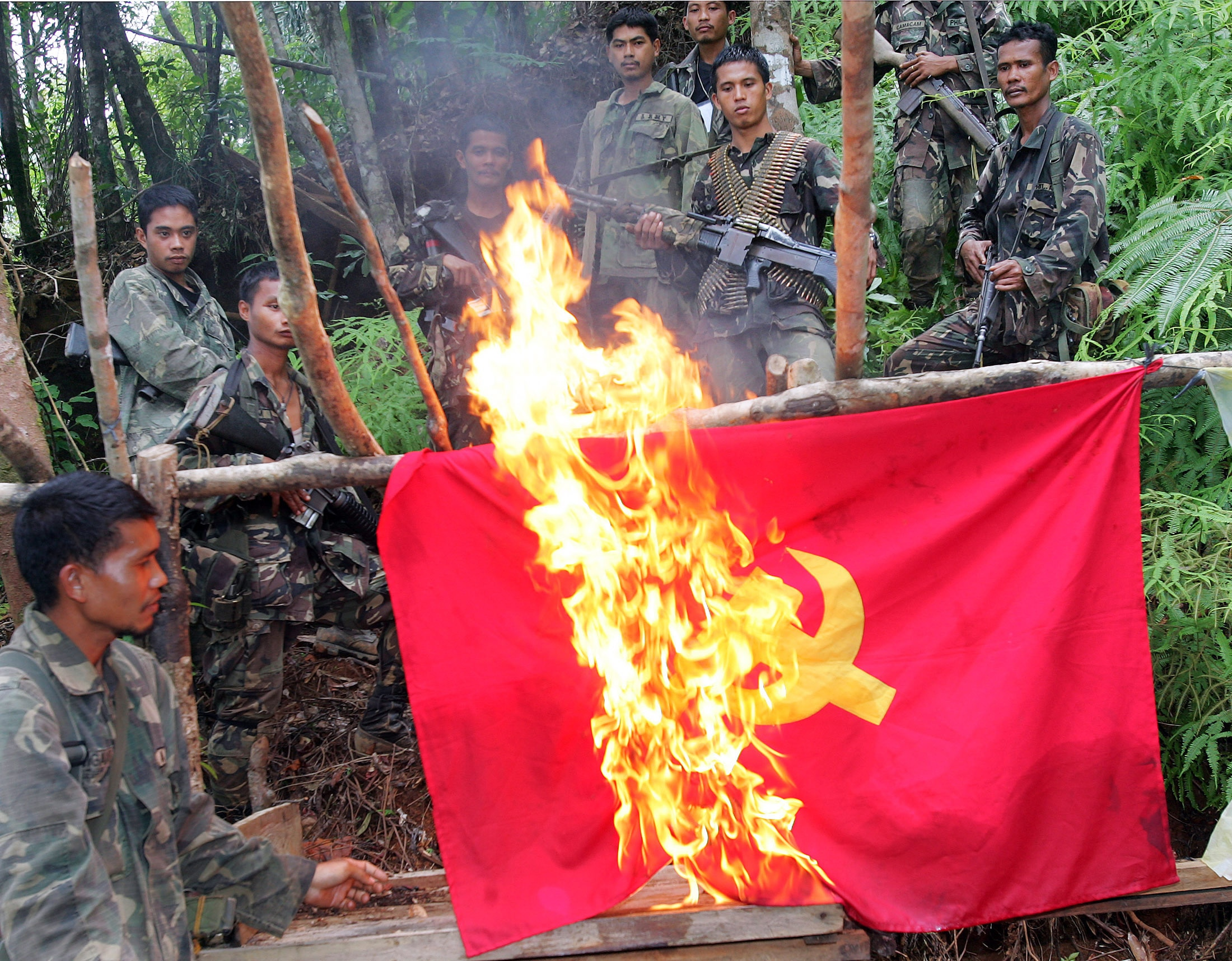 Philippine Army soldiers watch as they burn a communist flag in an abandoned rebel camp in the mountainous area of General Nakar.