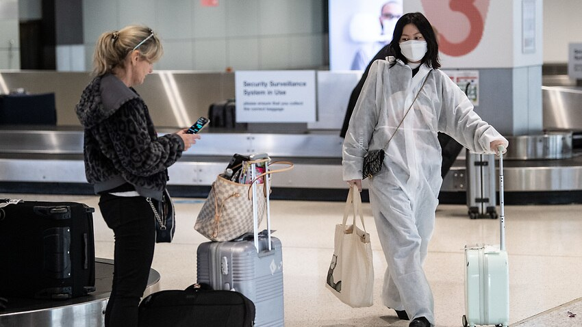 A passenger wearing a protective suit and mask collecting baggage after arriving on a flight from Melbourne.