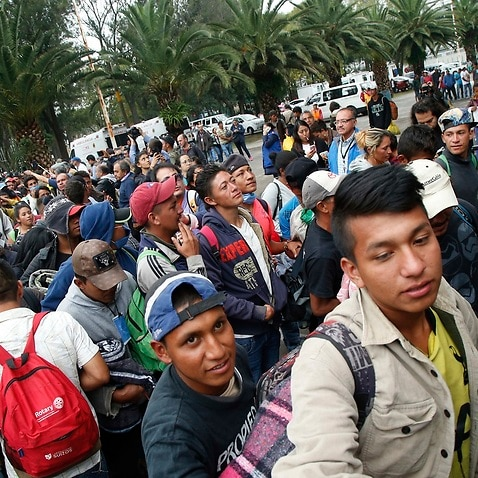 Central American migrants file into a sporting centre that has been turned into a shelter for them in Mexico City.