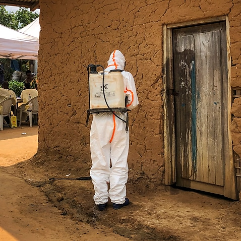 A worker from the World Health Organization decontaminates the doorway of a house in the village of Mabalako, in eastern Congo last month.