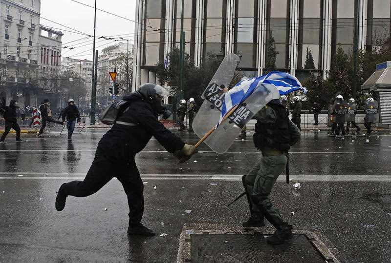 A protester clashes with riot policeman during a rally against the Prespes agreement between Athens and Skopje regarding the name 'Northern Macedonia'.