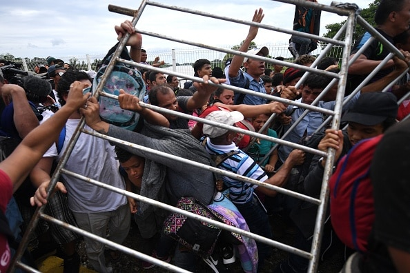 Honduran migrants remove a barrier at the Guatemala-Mexico international border bridge.
