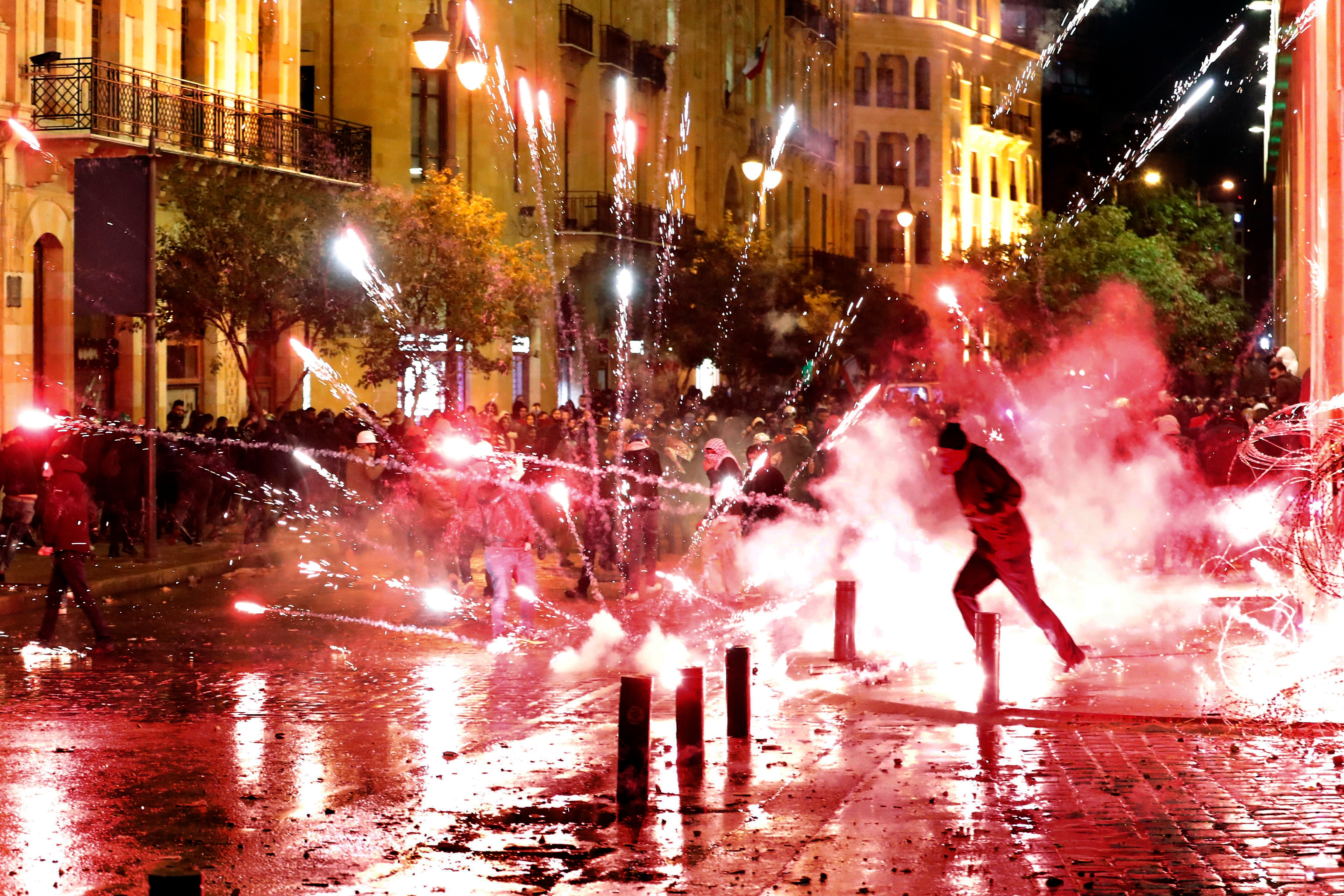 Anti-government protesters throw firecrackers at riot police.