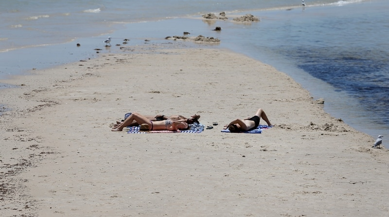 Beach goers sunbath on the sands of Henley Beach during a hot day in Adelaide, Thursday, January 3, 2019. Temperatures soared across South Australia today, climbing close to 50C in some regional towns. (AAP Image/Kelly Barnes) NO ARCHIVING