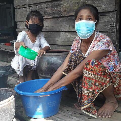 タンダールとその母親は、COVID-19から身を守るために手を洗います。