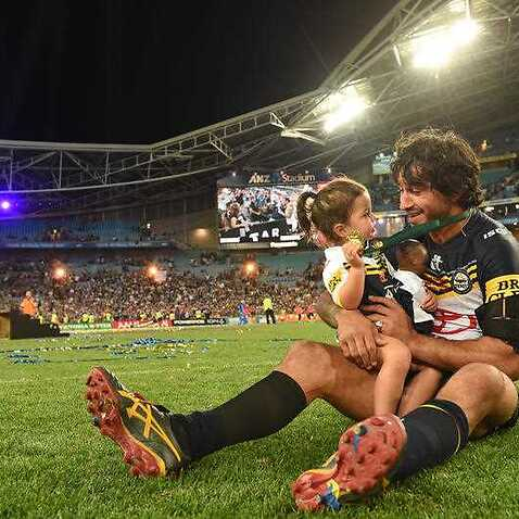 Cowboys captain Johnathan Thurston with daughter Frankie takes a quiet moment in the middle of the field after their win over the Broncos the NRL Grand Final. (AAP Image/Dean Lewins)