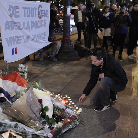 FRANCE, Paris: People bring flowers as they pay their respect at the site of a shooting on the Champs Elysees in Paris on April 21