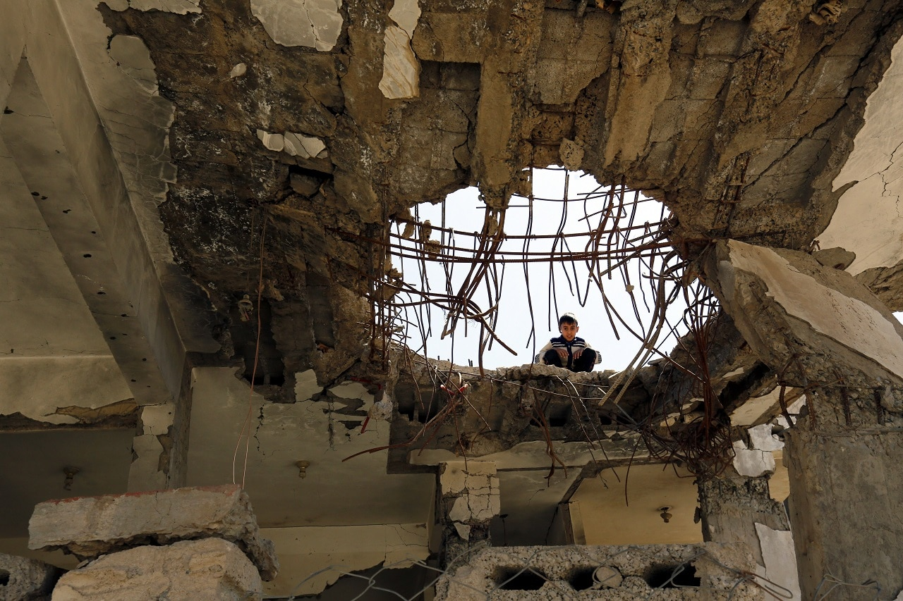 A Yemeni child looks through a hole in the ceiling of a severely damaged house that reportedly was destroyed by Saudi-led airstrikes.