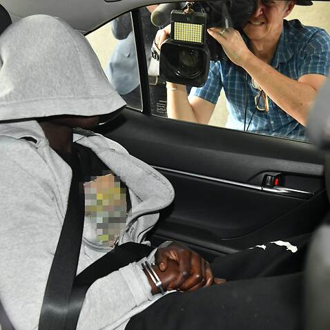 A man is seen being driven into the Brisbane Watchhouse by police.