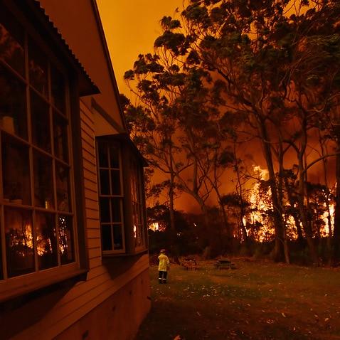 Firefighting crews battle a bushfire encroaching on properties near Lake Tabourie on the Princes Highway between Batemans Bay and Ulladulla.