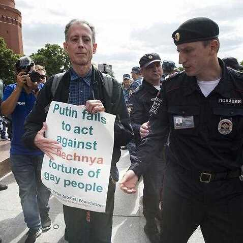 Russian police detain gay rights activist Peter Tatchell, as he holds a banner that read