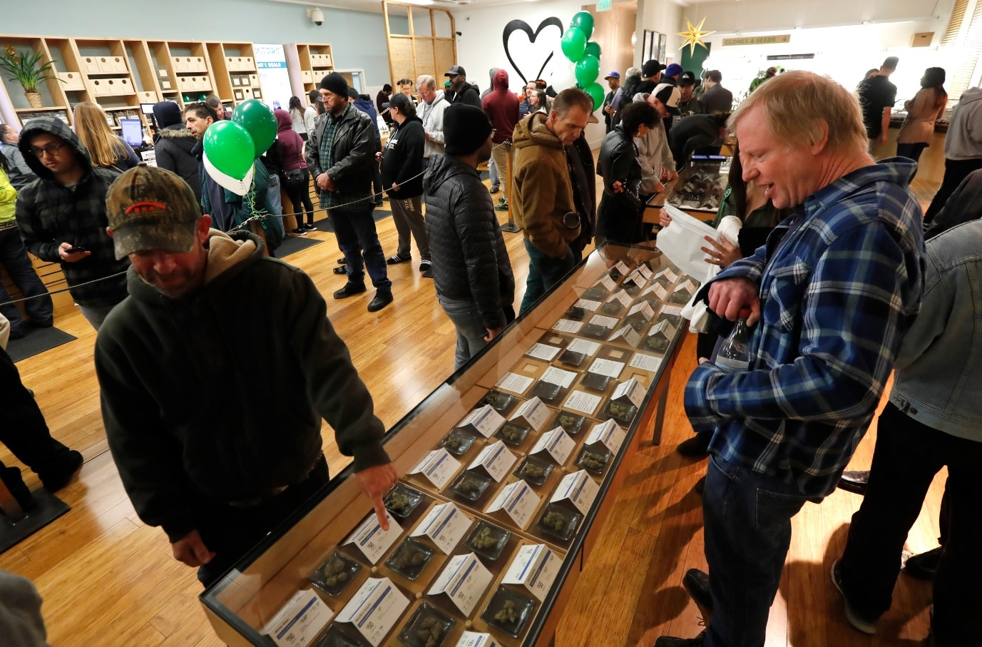 Customers check out cannabis samples on display while waiting in line at the Harborside cannabis dispensary in Oakland, California, USA (AAP)