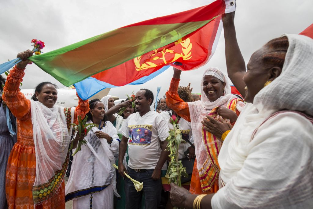 Eritrean women hold up the flag of Eritrea on July 18, 2018, to welcome passengers of the flight from Ethiopian capital Addis Ababa, upon their arrival at the Asmara International airport.