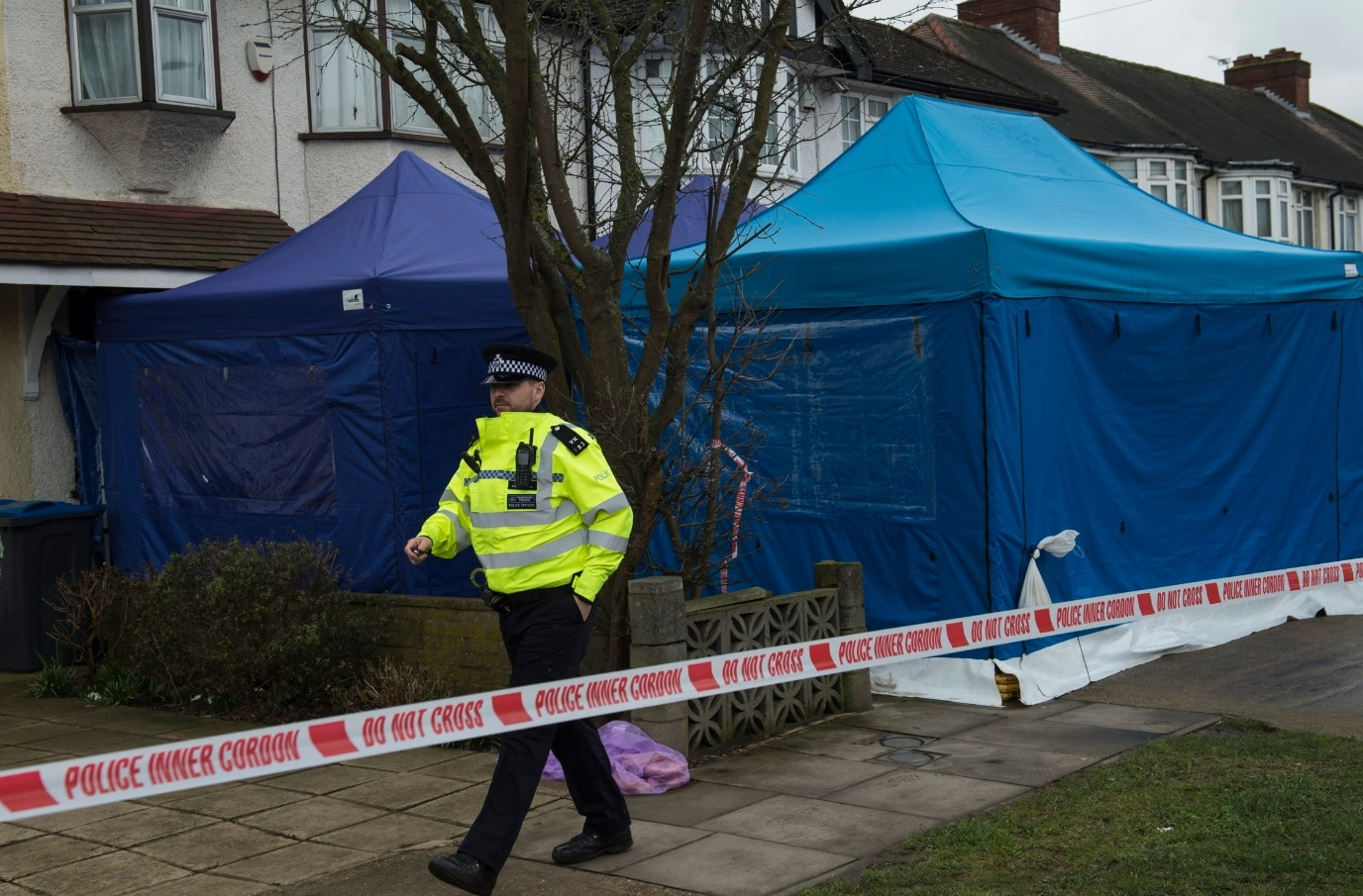 A police officer outside the scene of a property where the body of Russian businessman Nikolai Glushkov was found in New Malden South London Britain